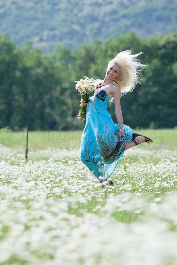Attractive blonde in chamomile field. Young woman with bouquet of flowers jumping in chamomile field stock photos
