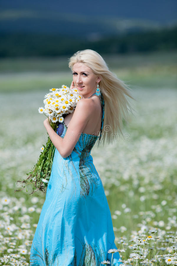 Attractive blonde in chamomile field. Young woman with bouquet of flowers in chamomile field royalty free stock photos