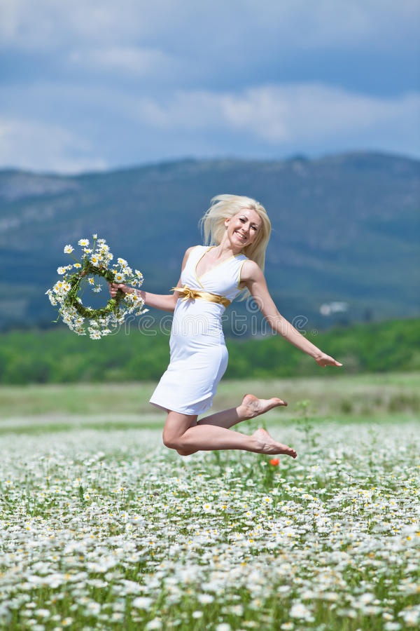 Attractive blonde in chamomile field. Young woman with wreath jumping on open air stock images