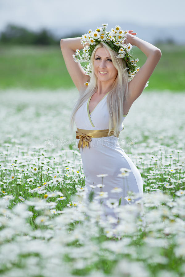 Attractive blonde in chamomile field. Young woman in wreath surrounded by chamomiles royalty free stock images