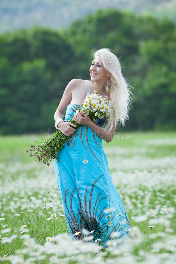 Attractive blonde in chamomile field. Young woman with bouquet of flowers walking through chamomile field stock images