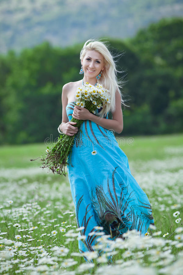 Attractive blonde in chamomile field. Young woman with bouquet of flowers walking through chamomile field royalty free stock photos