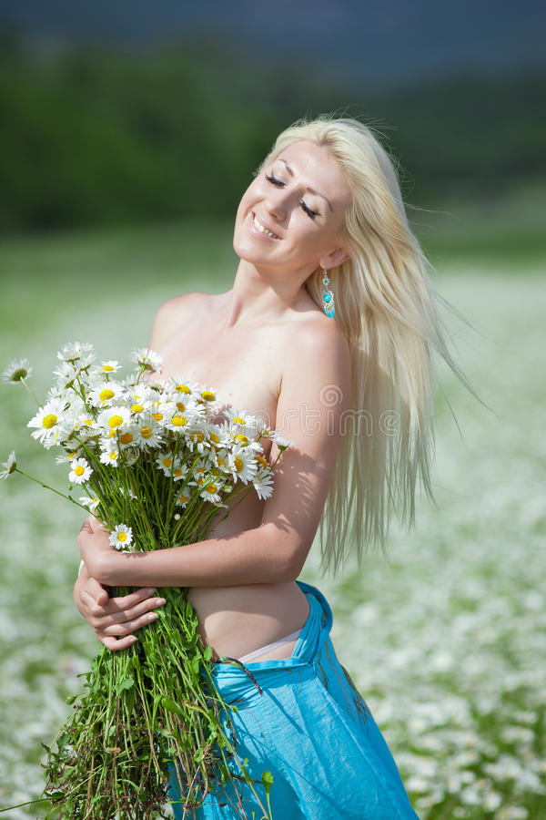 Attractive blonde in chamomile field. Young woman with bouquet of flowers posing in chamomile field stock photo