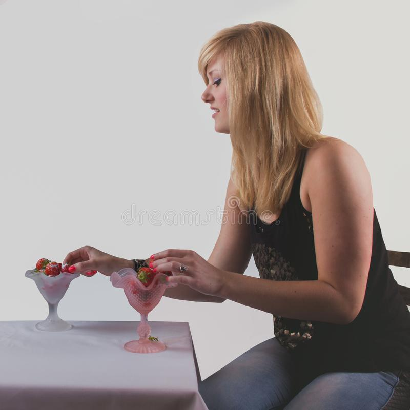 Attractive amazing blonde with two portion of strawberries on th royalty free stock images