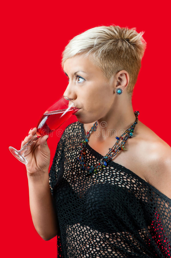 Attractive blonde girl holding glass of red wine stock image