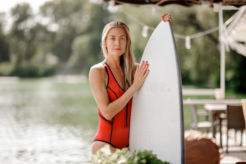 Attractive blonde girl holding a white wakeboard. Attractive blonde girl in red swimsuit holding a white wakeboard on the blurred background of a lakeside stock photos