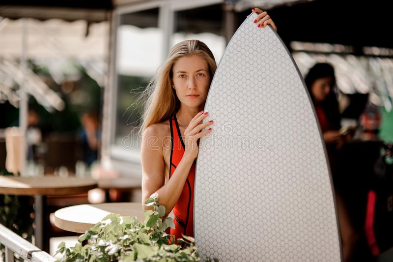 Attractive blonde girl holding a white wakeboard and looking at royalty free stock photo