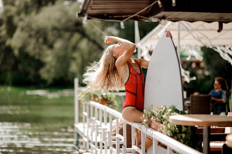 Attractive blonde girl holding a white wakeboard in a pier cafe. Attractive blonde girl in red swimsuit holding a white wakeboard in the pier cafe on the blurred royalty free stock photo