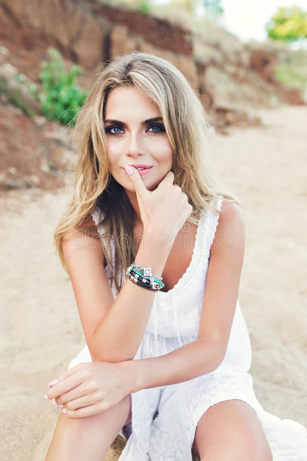 Attractive blonde girl with long hair and blue eyes is sitting on beach. She wears white dress, ornamentation. She is. Attractive blonde girl with long hair and stock image