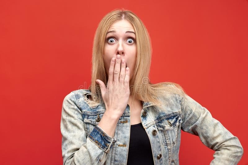 Attractive blonde girl with long hair in shock opens wide eyes and covers her open mouth with her hand. royalty free stock images