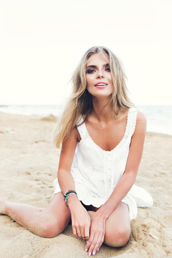 Attractive blonde girl with long hair is sitting on sand on beach. She wears white dress, ornamentation. She is looking. Attractive blonde girl with long hair is royalty free stock photo