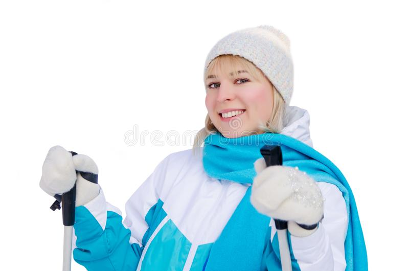Attractive blonde girl in sports jacket, hat and blue scarf and ith ski poles in her hands with smile looking at the camera. Isolated on white background stock photography
