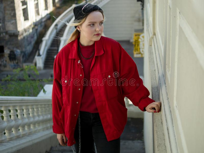 Attractive blonde hipster girl in a knitted black hat and red jacket is standing on the stairs under the bridge royalty free stock photography