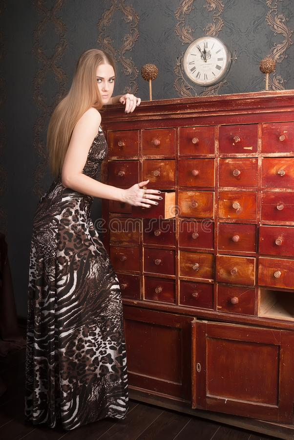 Beautiful young blonde haired woman opens drawer. Attractive blonde sad girl wearing beautiful long dress opens drawer of an old chest of drawers royalty free stock images