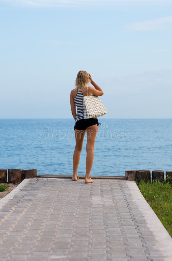 Attractive blonde standing on the beach. Evening royalty free stock photography