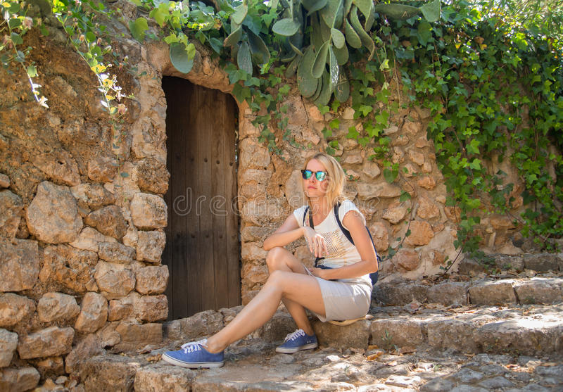 Attractive blonde tourist sitting on street and taking rest in t royalty free stock images
