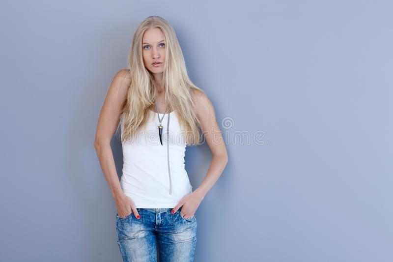 Attractive blonde woman by blue wall royalty free stock photo
