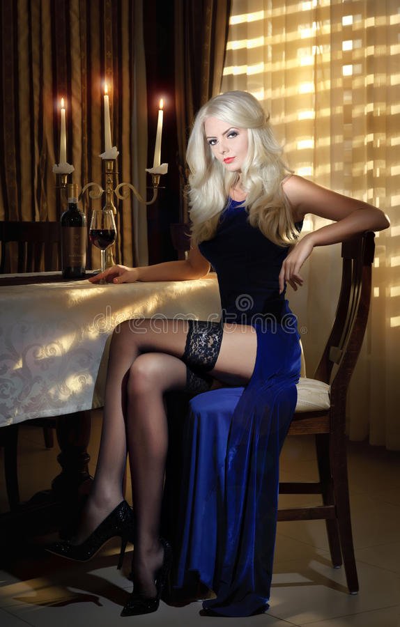 Attractive blonde woman in elegant long dress sitting near a table in a luxurious classic interior. Gorgeous blonde model royalty free stock photography