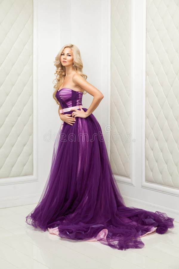 Attractive blonde woman in fashionable purple classic evening dress with makeup and long wavy hairstyle standing and posing near. Light wall and looking at stock photos