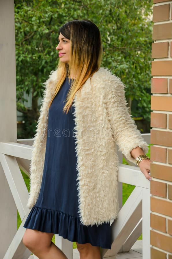 Attractive blonde woman of forty is standing on the porch of a c stock images