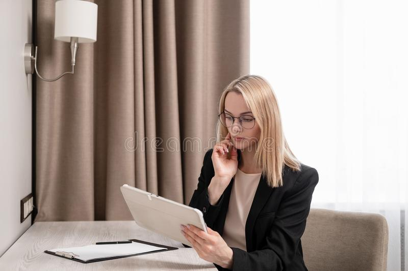 Attractive blonde woman in glasses and a business suit working on a tablet, talking on the phone and taking notes in a royalty free stock photography