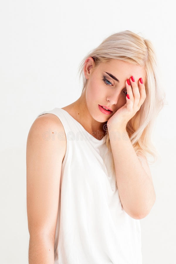 Attractive blonde woman with headache royalty free stock image