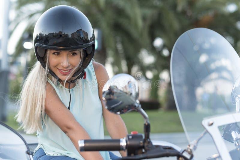 Attractive blonde woman with helmet n custom sidecar bike looking at mirror before trip royalty free stock photo