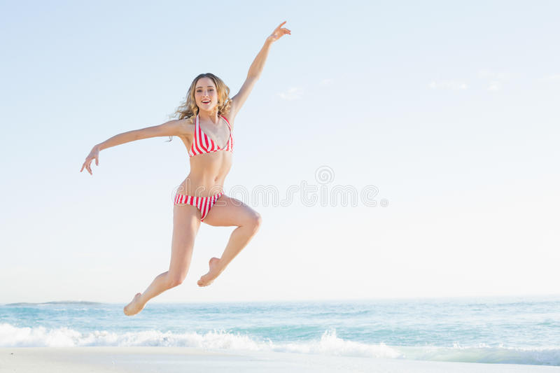 Attractive blonde woman jumping on the beach stock photography