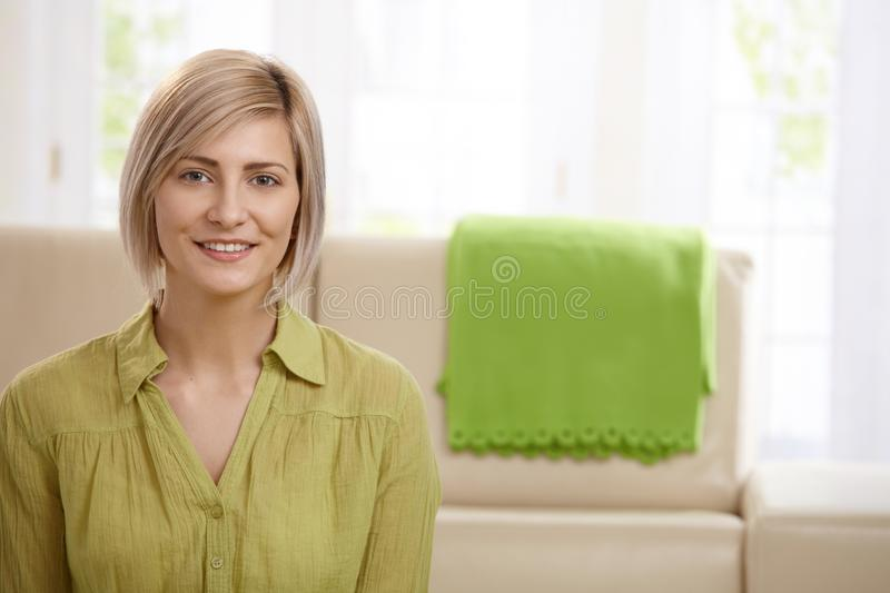 Attractive blonde woman. Portrait of attractive blonde woman smiling at home, sofa in background stock photography