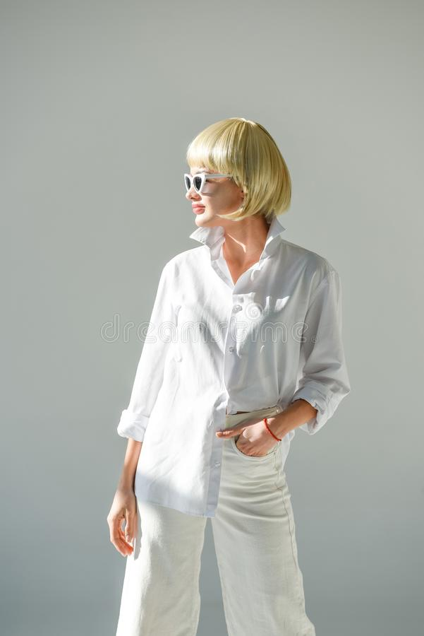 attractive blonde woman in sunglasses and stylish white outfit looking away stock photos