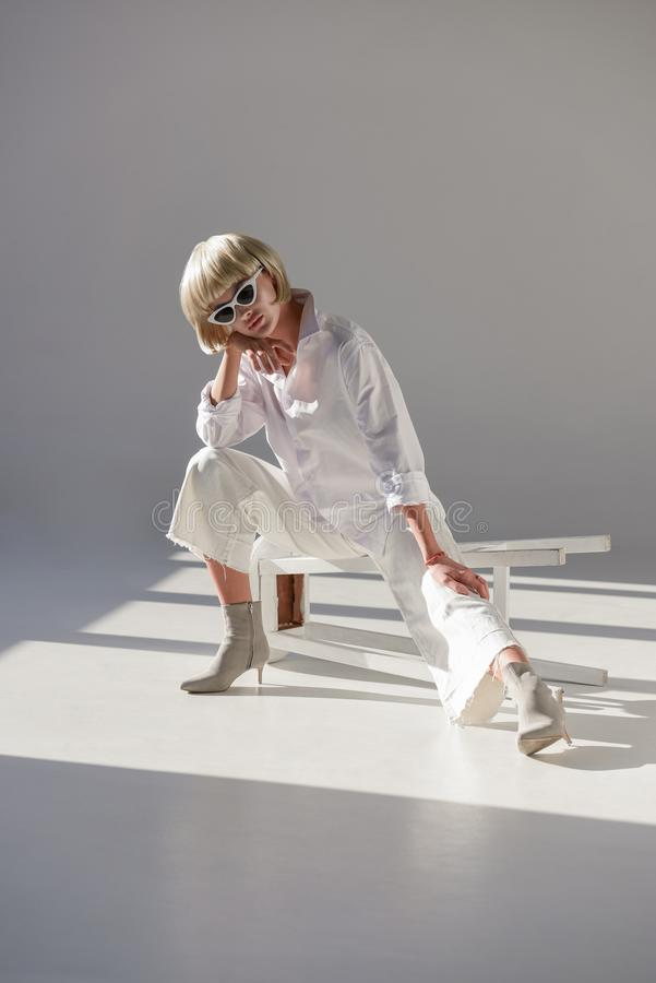 attractive blonde woman in sunglasses and stylish white outfit sitting on chair royalty free stock photography
