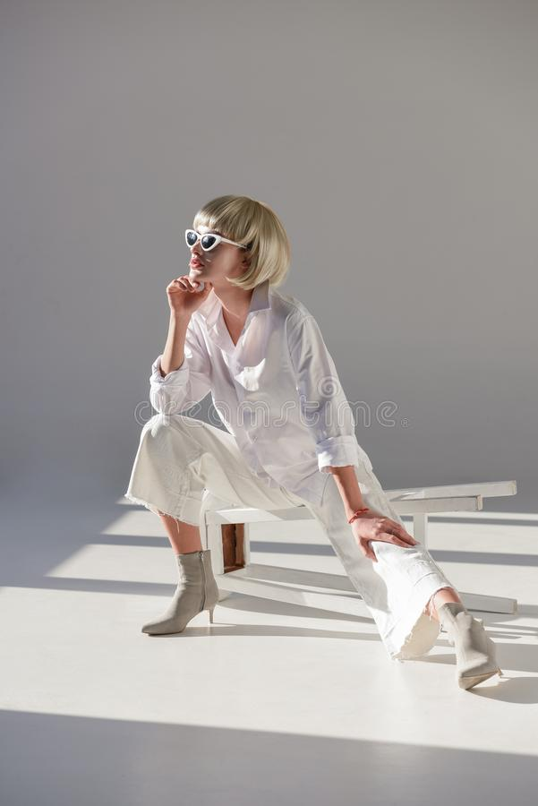 attractive blonde woman in sunglasses and stylish white outfit sitting on chair and looking away stock photo