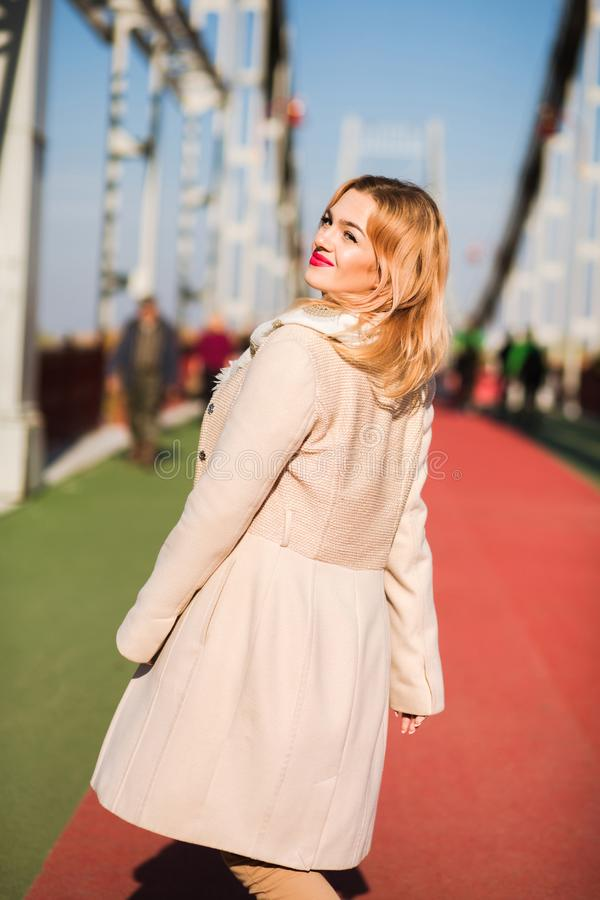 Attractive blonde model wears beige coat and white scarf, posing royalty free stock images