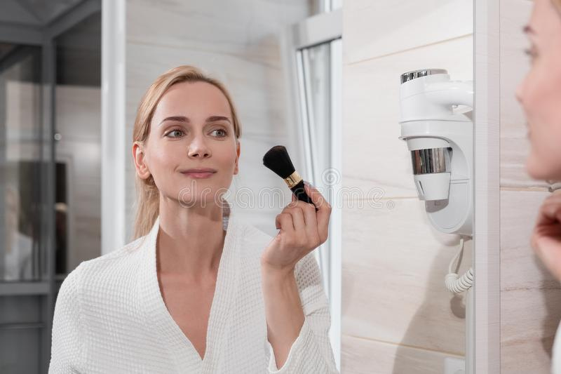 Attractive blonde woman in white bathrobe stands in bathroom by mirror. Applies makeup, speaks on mobile phone and. Drinks coffee. Morning fees, no time, doing royalty free stock photography