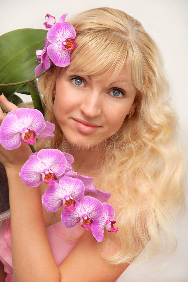 attractive blonde young blue eyes girl portrait with the beautiful lilac orchid branch stock photos