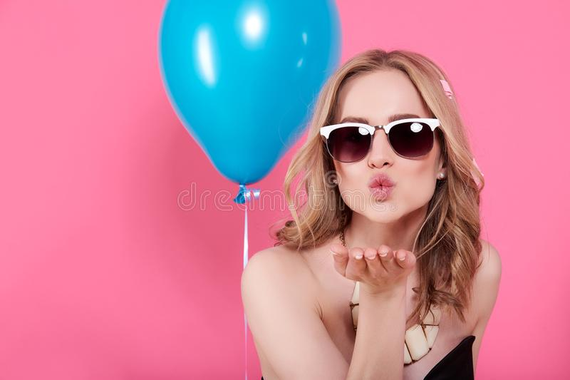Attractive blonde young woman in elegant party dress and golden jewelry celebrating birthday and blowing a kiss towards camera. Fashion portrait on pastel pink royalty free stock photo
