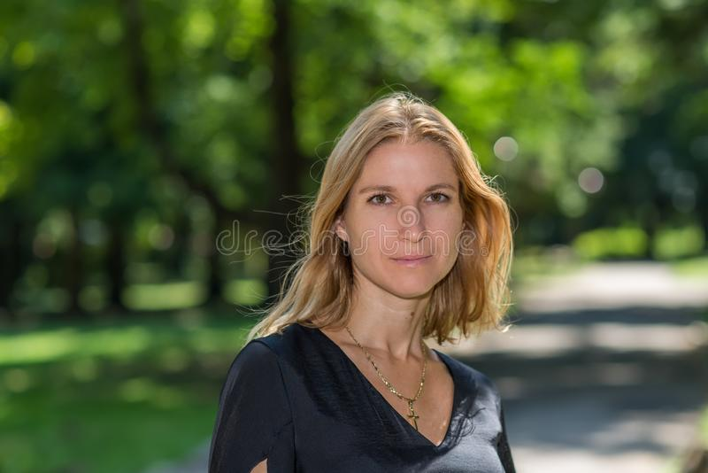 Attractive blonde young woman in a park stock photography