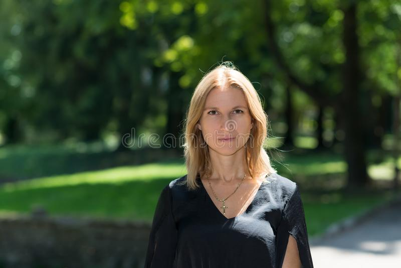 Attractive blonde young woman in a park royalty free stock photo