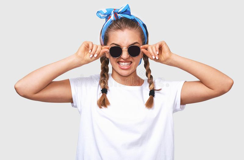 Attractive blonde young woman wearing trendy sunglasses, white t-shirt and blue headband, smiling broadly. Student girl going stock image