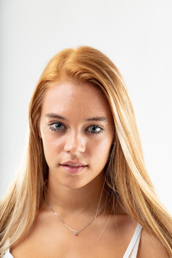 Attractive intense young woman staring at camera. Attractive blue eyed intense young blond woman staring at the camera, with parted lips in a close up frontal royalty free stock photo