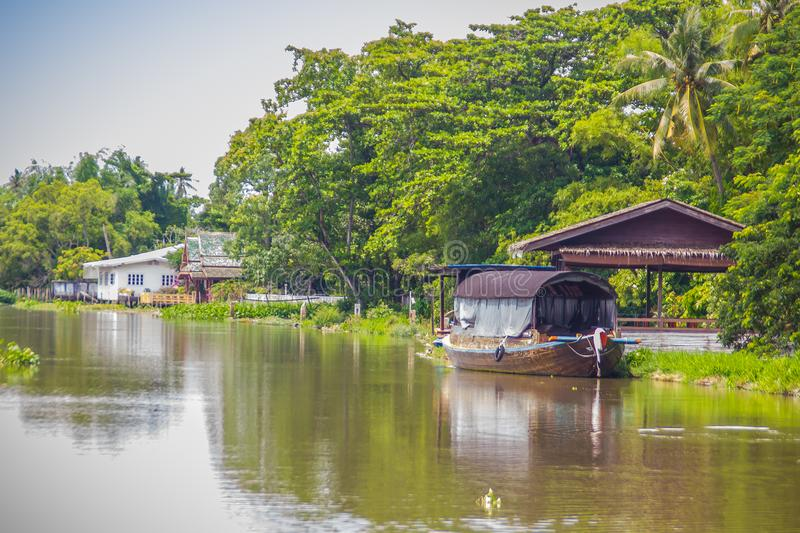 Attractive boat house on the river bank and the countryside scenery along Tha Chin river (Maenam Tha Chin), Nakhon Pathom, Thailan. D royalty free stock photos