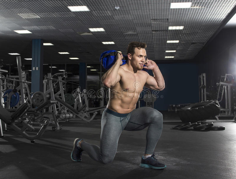 Attractive bodybuilder doing squats using fitness bag in modern royalty free stock image