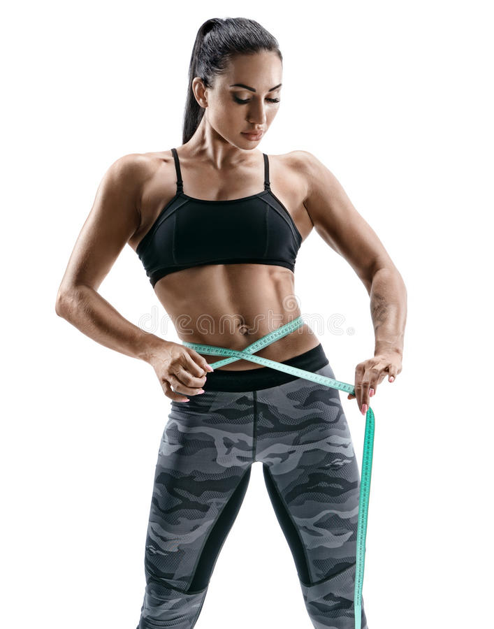 Attractive bodybuilder woman with tape measures the size of the waist stock photos