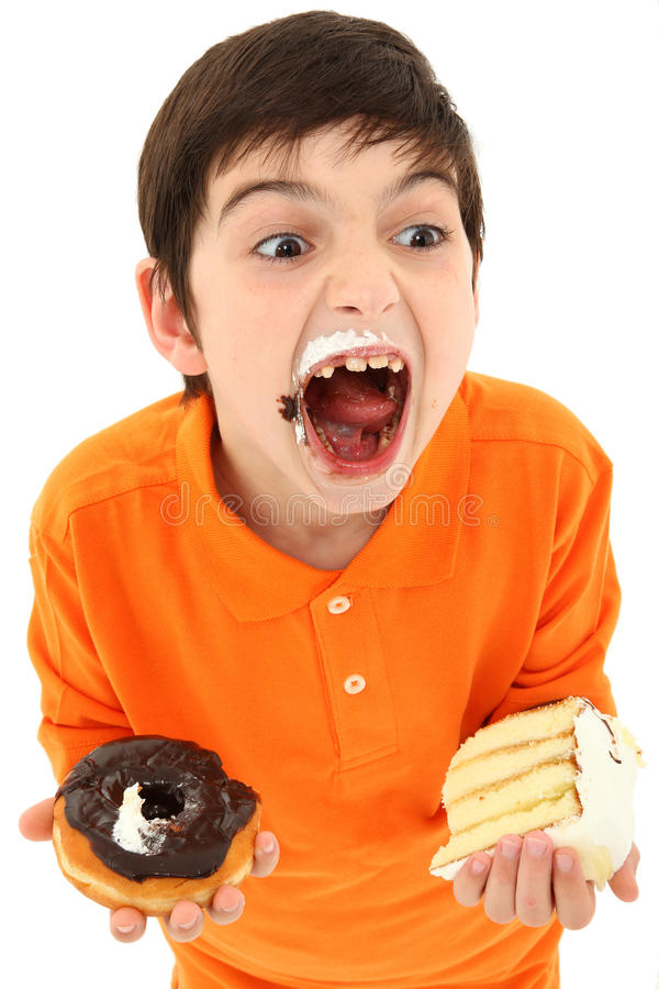 Attractive Boy Enjoying Sweets. Attractive 8 year old boy with insane expression and hands full of sweets over white royalty free stock photo