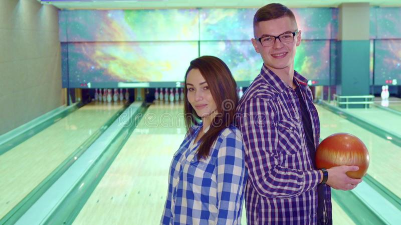 Boy and girl look at each other at the bowling. Attractive boy and girl looking at each other at the bowling. Nice brunette couple in checkered shirts turning royalty free stock photos