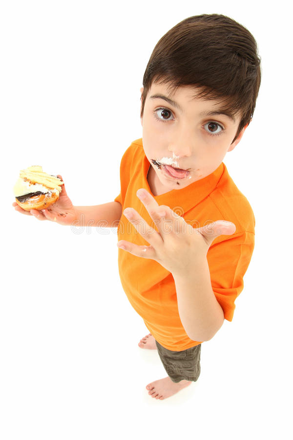 Attractive Boy Licking Chocolated Off Fingers. Attractive 8 year old boy standing with donuts and cake licking food off fingers royalty free stock photos