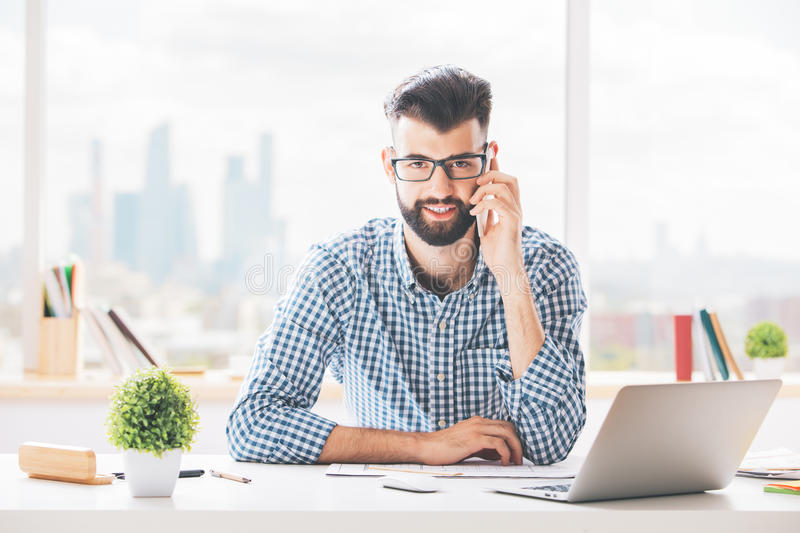 Attractive boy on phone. Attractive young boy sitting at his office desk with laptop, supplies, other items and talking on mobile phone. Communication concept royalty free stock images