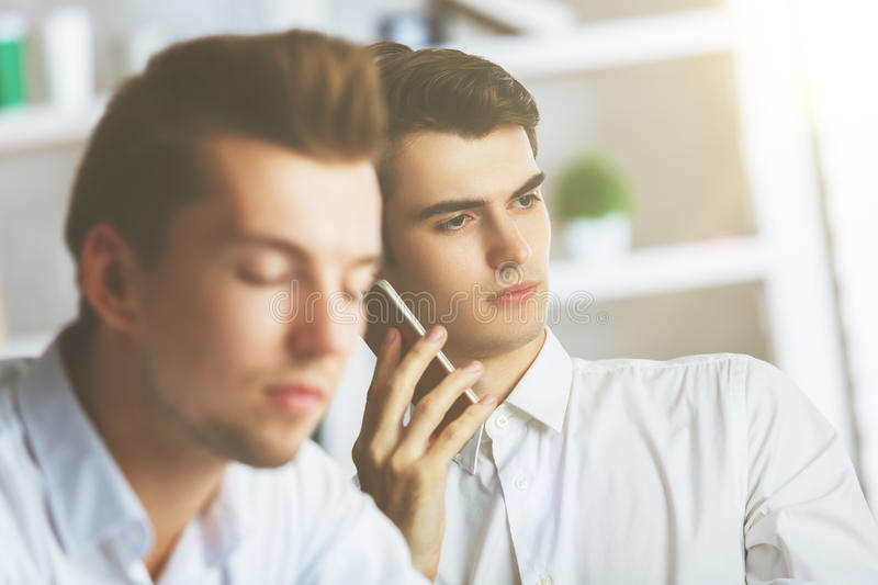 Attractive boys talking on phone. Close up portrait of two attractive european boys talking on phone at workplace royalty free stock photos