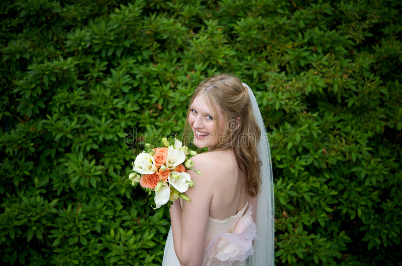Attractive bride against lush foliage royalty free stock image
