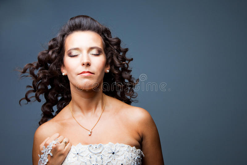 Attractive bride with long curly hair royalty free stock image